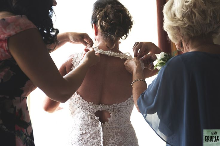 last minute adjustments to the dress.  Help is needed.  Weddings by Couple Photography. www.couple.ie