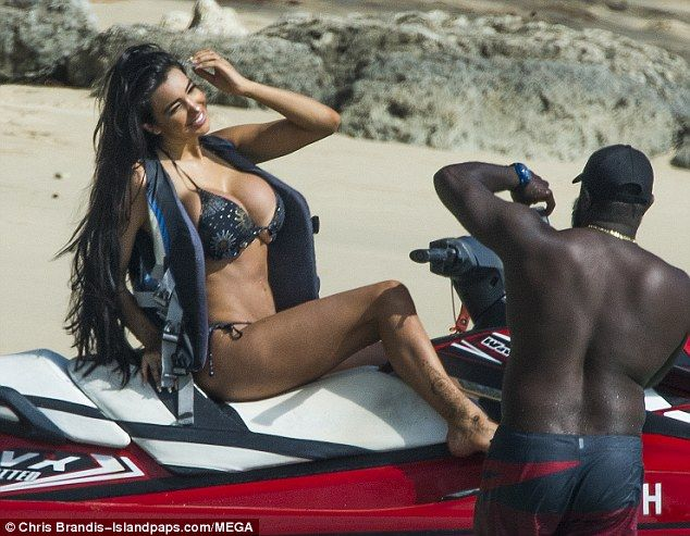 Busty display: Chloe Khan struggled to contain her curves in a tiny black and gold bikini as she posed on top of a red jet ski