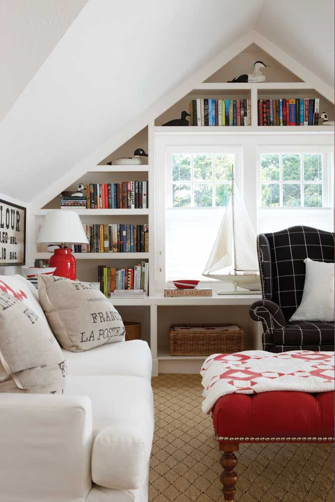The second-floor loft overlooks the living room and is a treasure trove of books and Americana.  Easygoing Elegance | New England Home Magazine