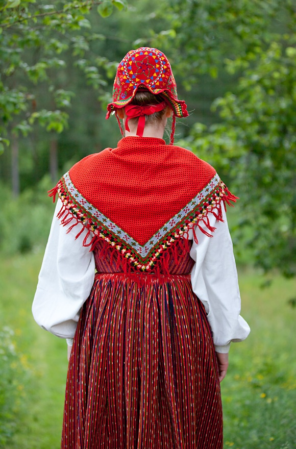 The back of an old Swedish folkdräkt in Näs. The embroidered fringed scarf and hat are of wool. The skirt and separate bodice are in two different red and black striped fabrics. Photo by Laila Duran