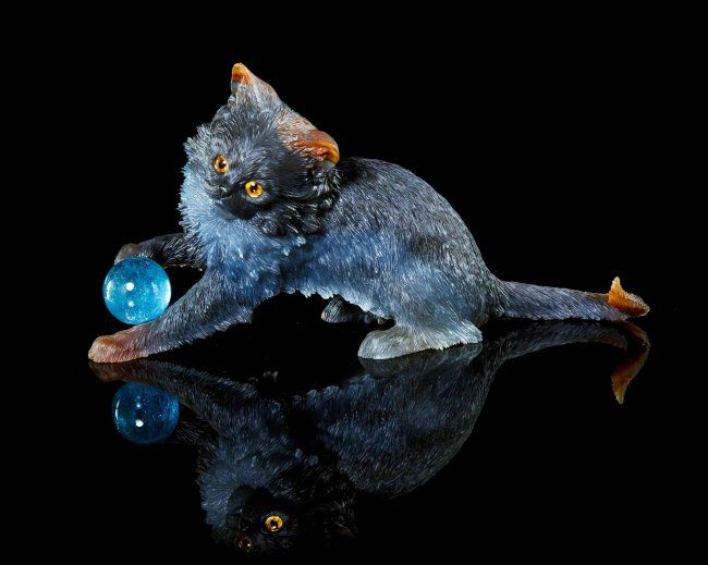 An Agate and Aquamarine Cat Carving.IdarOberstein,attributed to Alfred Zimmerman, carved from a superb piece of banded agate rough, the carving depicts a playful cat batting a deep blue aquamarine sphere, the body intricately carved with fur detail and exhibiting excellent color isolation at the brown ears, tail and paws against the deep blue and gray blue body, eyes inset with hand painted elements. 11.43 x 4.57 x 5.97 cm. : Lot 207