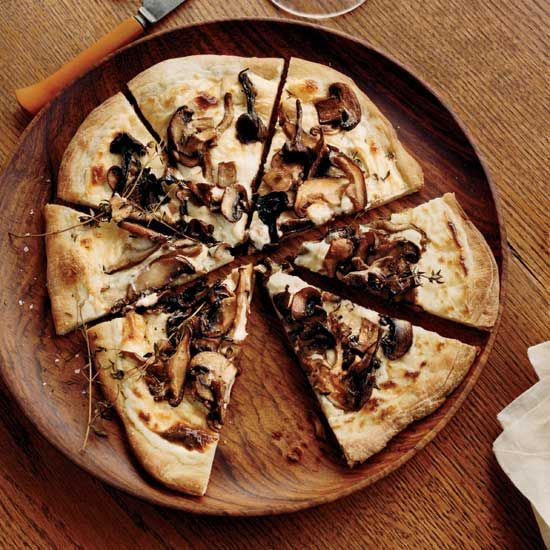 Mushroom–and–Goat Cheese Béchamel Pizzas | To give these individual pizzas an extra-luxe topping, Andres Barrera makes a velvety béchamel sauce with goat cheese and freshly grated nutmeg, then adds dollops of sautéed mushrooms.