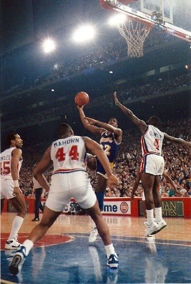 Adrian Dantley, Rick Mahorn and Joe Dumars try to block Magic Johnson's shot