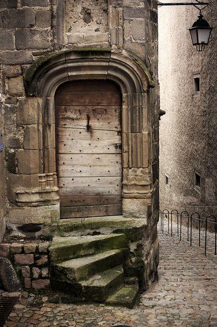 Petite portes en bois et petit escalier de pierre. Auvergne, France