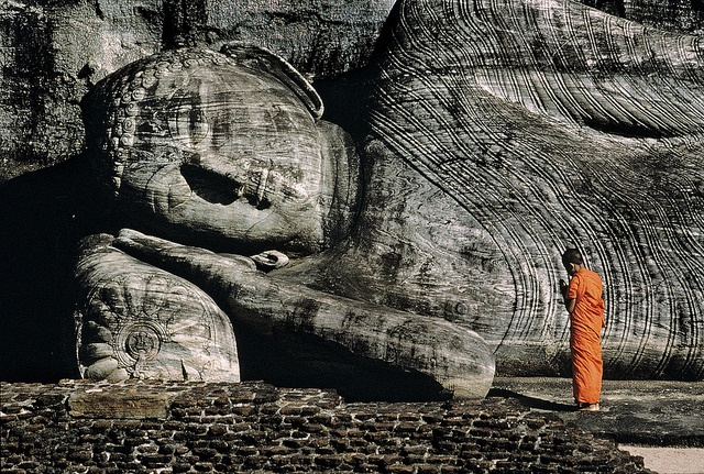 Buddhist monk praying near reclining Buddha, Polonnarvwa, Sri Lanka, 1995, by Steve McCurry
