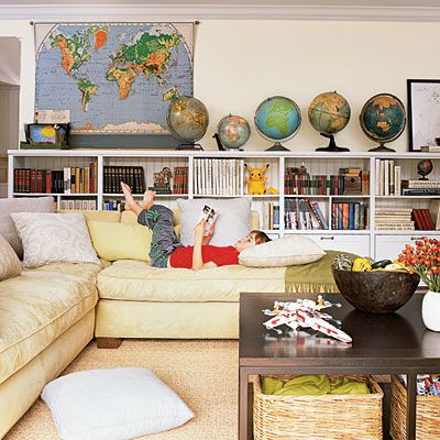 kids' space.  wall to wall kid-height bookcases w/ cabinets at the base.  comfy sofa to read on.    Besides the classroom map (love it), a gallery of the kids' art would look great above the bookcase
