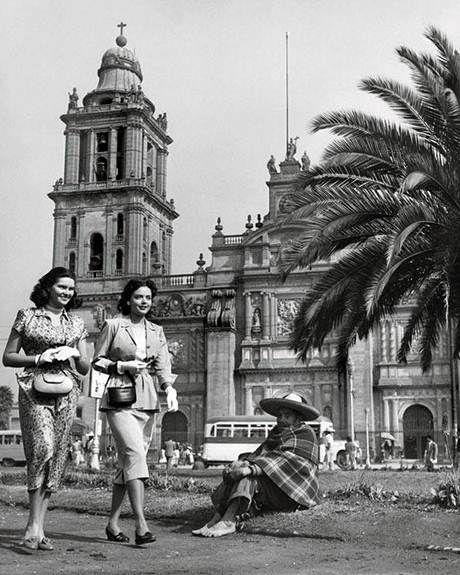 Zocalo Capitalino con jardineras y Palmeras, un par de mujeres vestidas elegantemente con todo y guantes y sentado un persona de nivel economico mas bajo, con zarape, sombrero de palma y sin zapatos. Al fondo la catedral de Mexico y la vialidad de Mexico en los años 40´s