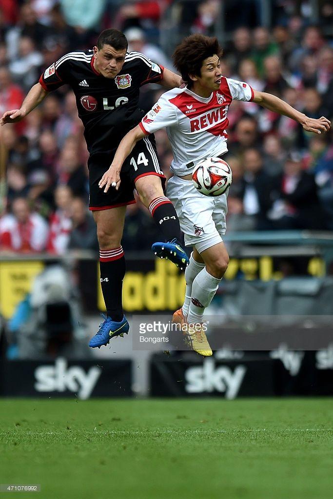 Kyriakos Papadopoulos of Leverkusen battles for a header with Yuya Osako of Koeln during the Bundesliga match between 1. FC Koeln and Bayer 04 Leverkusen at RheinEnergieStadion on April 25, 2015 in Cologne, Germany.