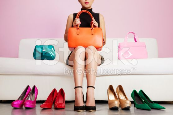 Woman sitting on sofa with colorful shoes and bags. Shopping. royalty-free stock photo