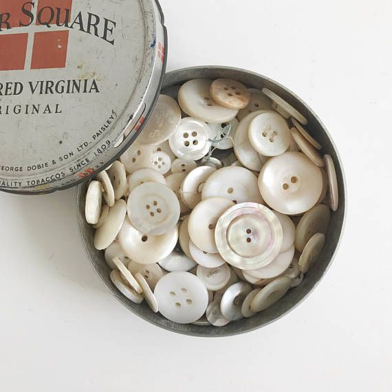 A lot of 150 mixed, assorted vintage and antique pearl or shell buttons in a Four Square tobacco tin. This lot of 150 buttons contains a variety of sizes and styles. Most of the buttons have been previously used and may show signs of age and wear such as small chips and worn edges. They are perfectly imperfect! There is at least 150 buttons in the tin which measures 10.5cm in diameter x 2.5cm in height. Due to the difficulty in accurately calculating combined shipping rates I guarantee to…