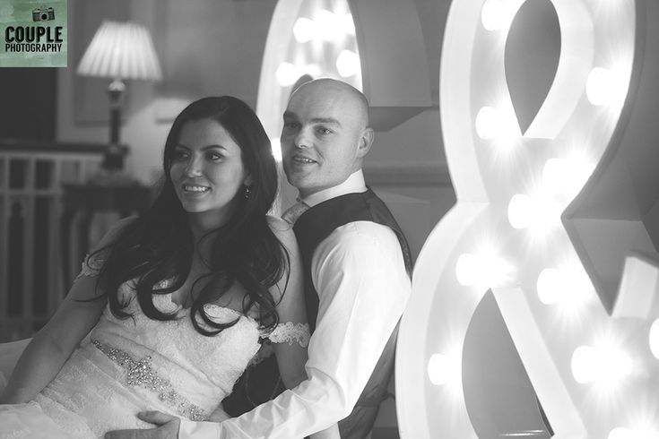 The bride & groom beside their G&S sign lighting up their reception room. Weddings at Cabra Castle photographed by Couple Photography.