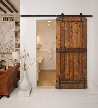 This bathroom door was salvaged from a sheep barn in New Hampshire. Using sliding barn door hardware ($100) meant the door didn't have to be cut to fit the opening.