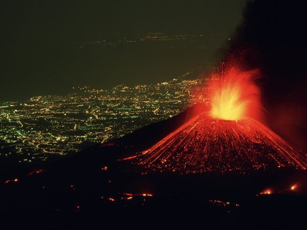 Perched above the lighted city of Catania, Italy, Mount Etna hurls a fountain of fire skyward as rivers of lava spill down its flanks. In spite of its dazzling displays, Mount Etna is a relatively safe volcano with rare, compact eruptions and slow-flowing lava that gives people a chance to escape.
