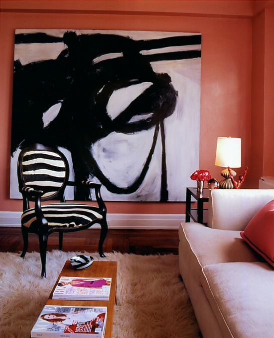 Franz Kline painting, Victorian chair upholstered in a textured zebra print, shaggy rug and coral pink walls.