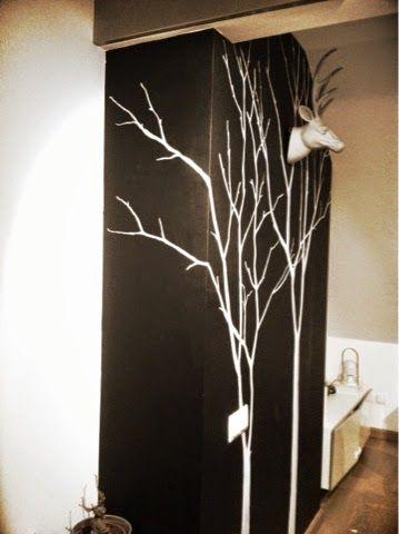 Una pared con pintura de pizarra y árboles dibujados con tiza líquida.