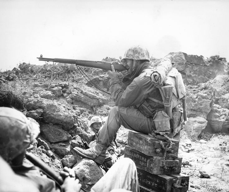 "On Iwo Jima, a U.S. Marine aims his M1 Garand rifle at the enemy with an uncertain grip. His helmet cover identifies him as ""Martin 1"". Note the cases of Japanese ammo used by him for his perch. (1945)"