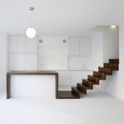 Surreal. Like an Escher drawing realised.  A dark walnut staircase merges with a kitchen counter and a bathtub inside this renovated apartment in Mayfair, London, by architecture studio KHBT