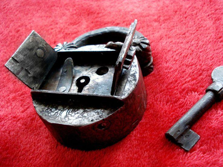 Um den Bügel zu öffnen muss zuerst ein kleiner Stift unten rechts gedrückt werden, so öffnen sich 2 Türchen vom Schloss, die nach außen springen. Danach kann man mit Hilfe des Schlüssels das Schloss öffnen.