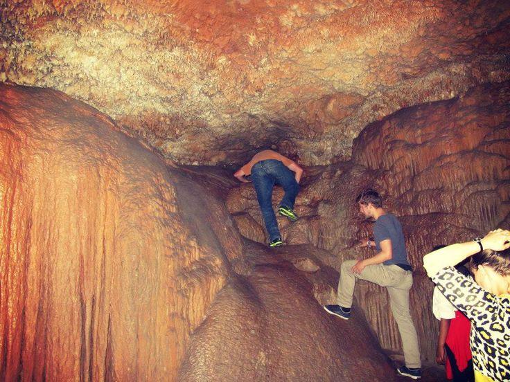 Climbing through Devils Chimney at Cango Caves
