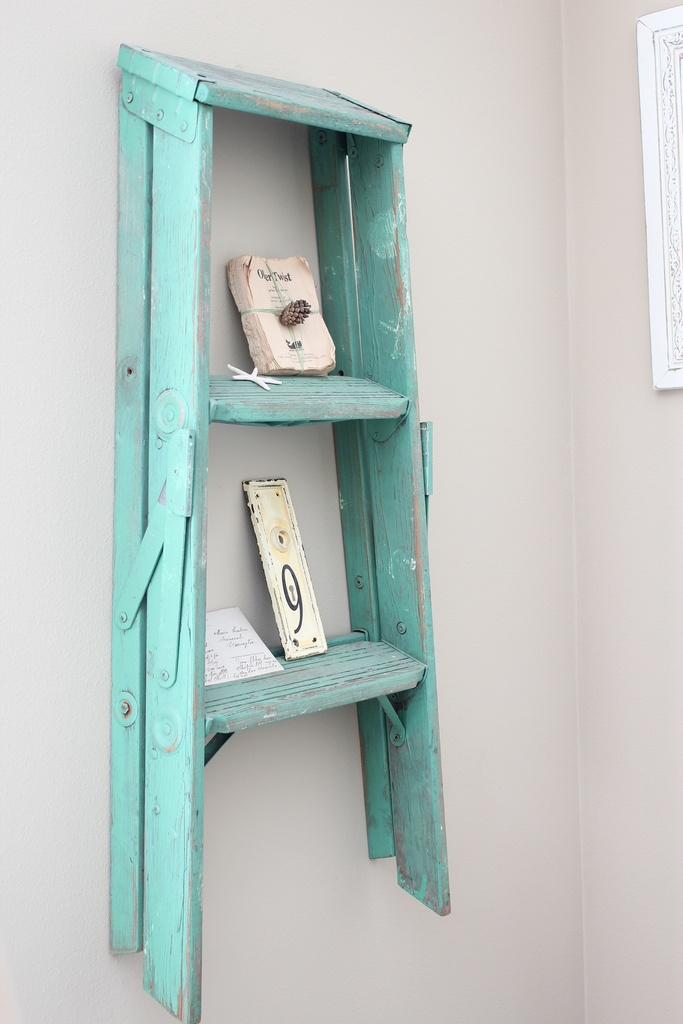 We have a small old ladder like this and it's too wobbly to use. Never thought to paint it shabby chic and hang it on the wall ... until now!!