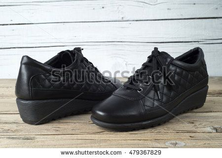 Pair of woman shoes on old wooden table