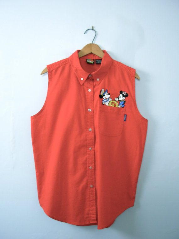One vintage 1990s Disney shirt, Mickey and Minnie red sleeveless shirt, oxford shirt, womens size large  - Pointed collar with 2 buttons to hold down the points. - 7 white button closures down the center front of the shirt, with Mickey written on them. - 1 pocket with button closure. - Embroidered Mickey and Minnie mouse, nautical themed. - Pull tab in the back center of the shirt. - Color scheme: vivid red.  | CONDITION | A+. Gently used vintage item.  | BRAND | Mickey Unlimited. Made in…