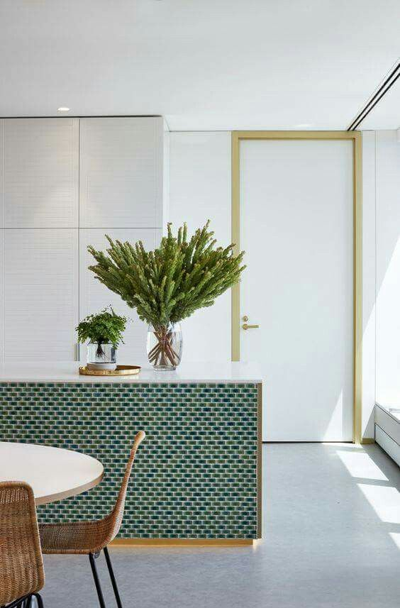 Contrast of texture with the wicker chairs, the green floral piece and the tiling of the island.