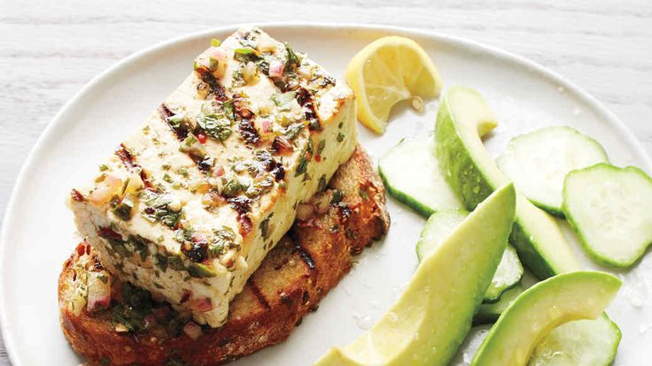 """Vegans, take heart: Here's an appealing dish for the grilling season. Pressed tofu is marinated in chimichurri -- an Argentinian herb sauce that's usually served with steak -- and then grilled with slices of wholegrain bread. Cucumbers and avocado round out the meal. This recipe comes from our book """"Clean Slate: A Cookbook and Guide."""""""