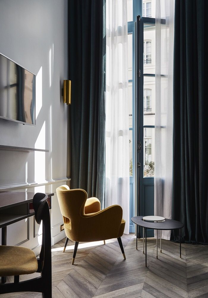 The teal curtains with golden toned chair. colorful without being too much