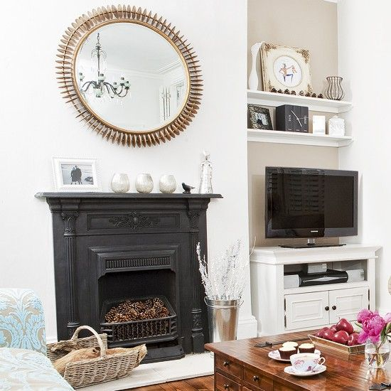 Classic neutral living room.  The black fireplace is at the heart of this classic scheme. The white walls and pale blue sofa let it take centre stage, while the wooden floor and furniture warm up the look.