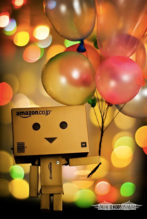 Amazon box guy smiling and holding a bunch of balloons.