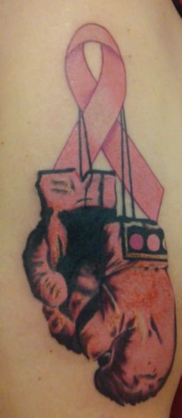 A Breast Cancer Survivor Tattoo with a pair of boxing gloves to indicate their fighting spirits against it as a cancer survivor!