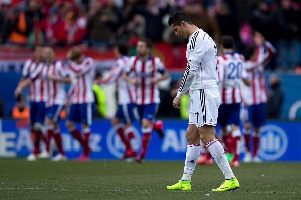 Cristiano Ronaldo of Real Madrid CF reacts defeated as behind Mario Mandzukic of Atletico de Madrid celebrates scoring their fourth goal with teammates during the La Liga match between Club Atletico de Madrid and Real Madrid CF at Vicente Calderon Stadium on February 7, 2015 in Madrid, Spain.