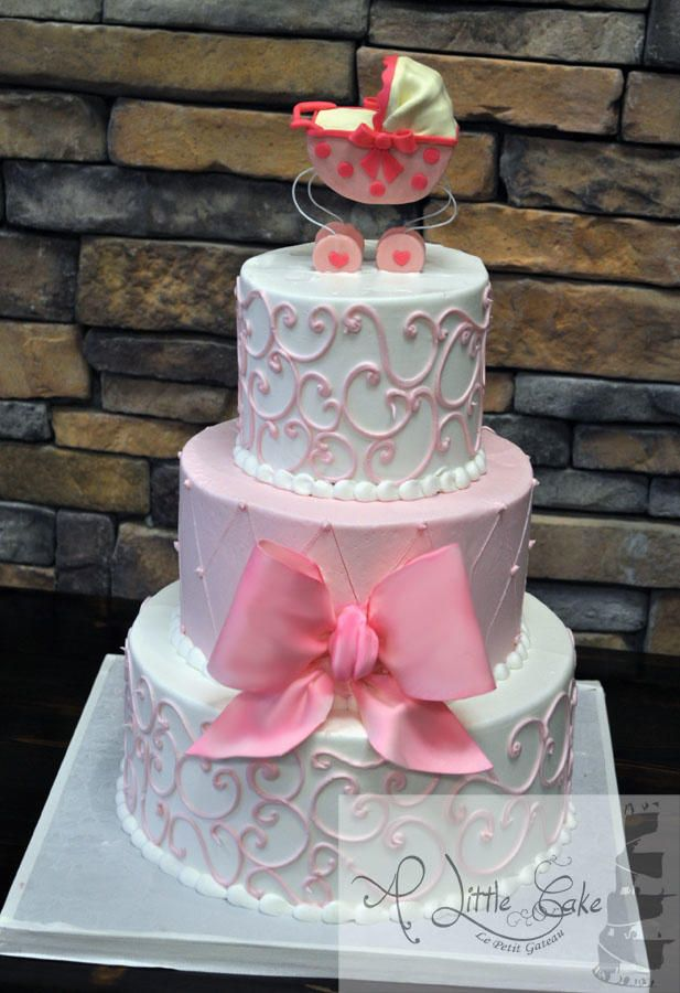 Pink Baby Girl Shower Cake ~ 3 tiers iced with a smooth buttercream. The white pearl boarders were piped on the bottom of each tier. the 2 white tiers are decorated with a pink swirl filigree and the middle tier has a quilting pattern and a pink sugar bow ~ all edible