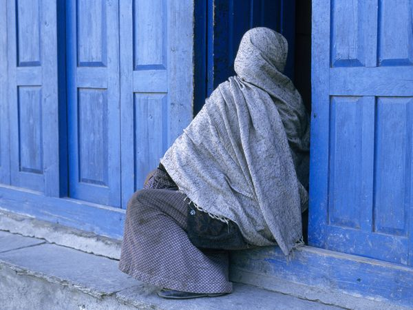 A veiled Nepali woman, covered head-to-toe in shades of blue, pauses to rest in a colorful doorway in one of the small Himalayan hill towns found in Nepal's Anapurna region