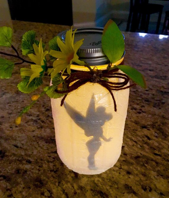 7 inch tall Mason Jar with Tinkerbell silhouette illuminated from within by a tea light. A touch of glitter and floral decorations on the outside make this fairy jar perfect for home or party decor.