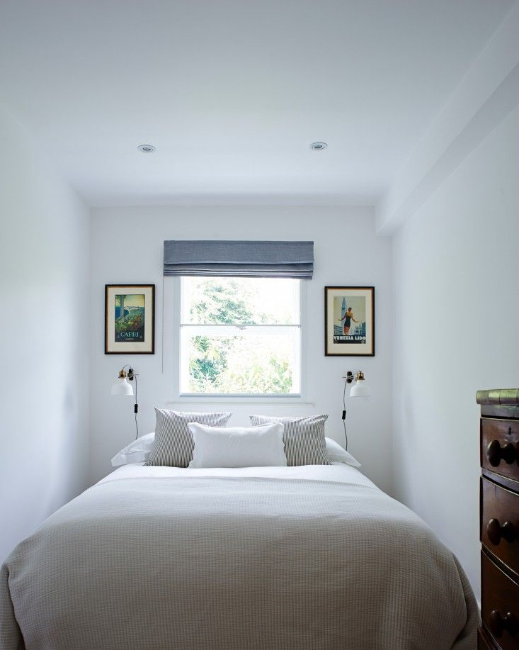 Twin pictures and wall mounted Ikea lamps in guest bedroom of Isabel and George Blunden London renovation | Remodelista