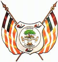 [Orange Free State coat of arms] behind the shield on two staves in saltire with ball and spear point Or, two flags of the same Republic draped on both sides, each with seven stripes visible, alternately white and orange and a canton of three stripes, red, white and blue.