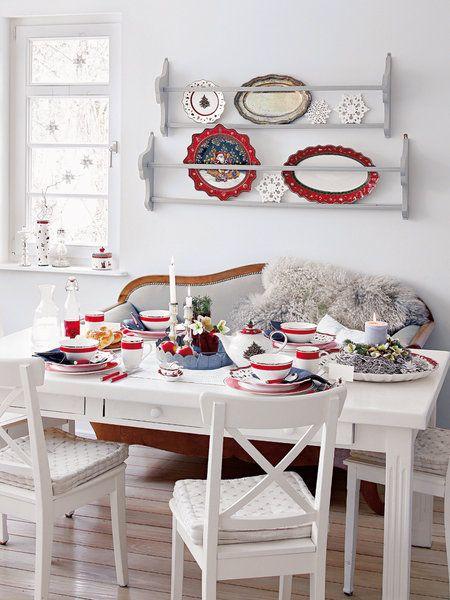 Una mesa navideña decorada en blanco y rojo
