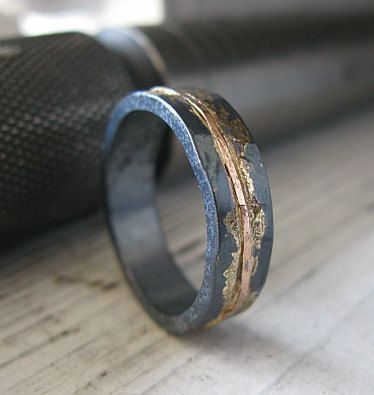 This design is simple and understated, yet rustic and OOAK. The ring is sterling silver, hammered for texture. There are some 14K yellow gold accents, and a river of 14K rose gold extends around the ring in the center of the band. Finally, the ring is oxidized to a dark gray, then lacquered.  It is 5mm wide and about 1.6mm thick.  This design is an edgy wedding band or chic fashion ring - for man or woman! Comes gift boxed and with a Hot Rox gift pouch.  **Oxidation is not permanent! This…