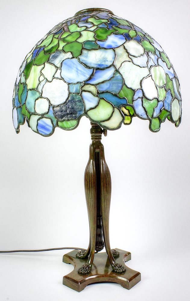 """Lot 1, An important Tiffany Studios, c.1905, table lamp, the telescopic bronze base with lions claw feet, the base stamped Tiffany Studios - New York- 481, with Edison patent light fittings stamped 250v.50 C.P. with Bryant bakelite fittings. The domed snowball style shade stamped to the interior Tiffany Studio - New York 1571-5 26"""" - 32"""" in height, sold for £35,000"""