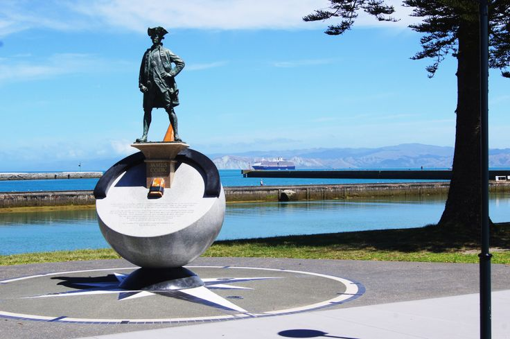 The Captain Cook iconic statue in Gisborne with a cruise ship in Poverty Bay.