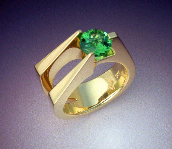 This heavy 18k gold womans ring features a beautifully cut, vibrant green Tourmaline weighing 1.3 carats. This is a fairly simple, tall