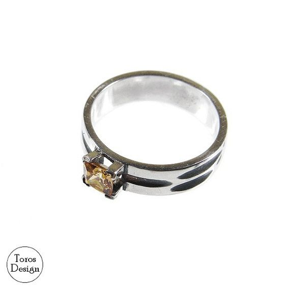 Ring with a square zircon. Handcrafted with sterling silver. Zirconia has a delicate, yellow-orange shade. The ring has oxidated pits.