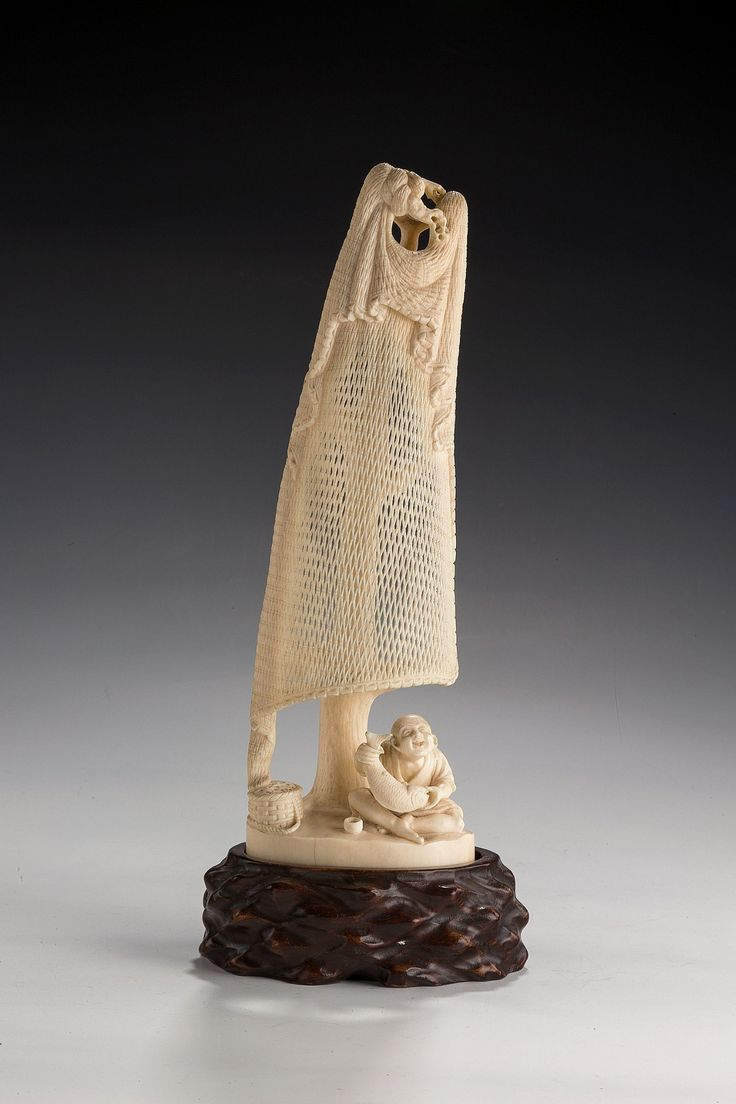 JAPANESE IVORY OKIMONO OF A FISHERMAN // A fine Japanese ivory okimono of a fisherman sitting on the floor holding a fish, above him suspended from a tree is his drying net, on a wooden stand. Signed. -