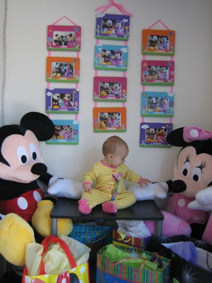 Since my daughter was a week old we took pics of her every month with her huge stuffed Mickey and Minnie to see her growth over the months. For her 1st birthday I framed them all of them in those unfinished $1 frames from Michaels and strung them on their $1 value ribbon. Her theme was Minnie's Garden so each frame was hand painted in coordinating colors complete with polka dot flowers and hidden Mickeys.