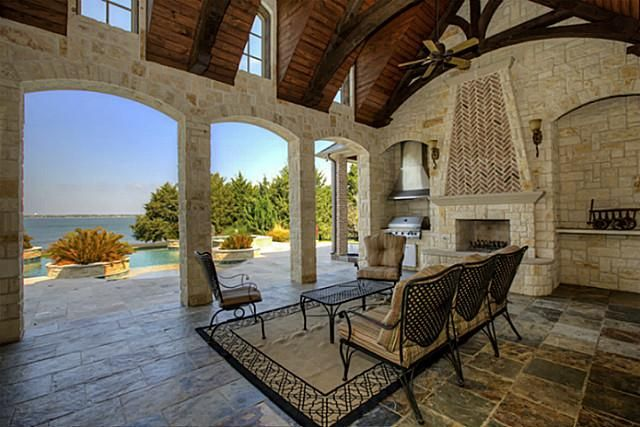 An open and waterfront outdoor living area with views of the home's infinity edge pool and spa. The space features an outdoor kitchen and fireplace. Heath, TX Coldwell Banker Residential Brokerage $2,275,000