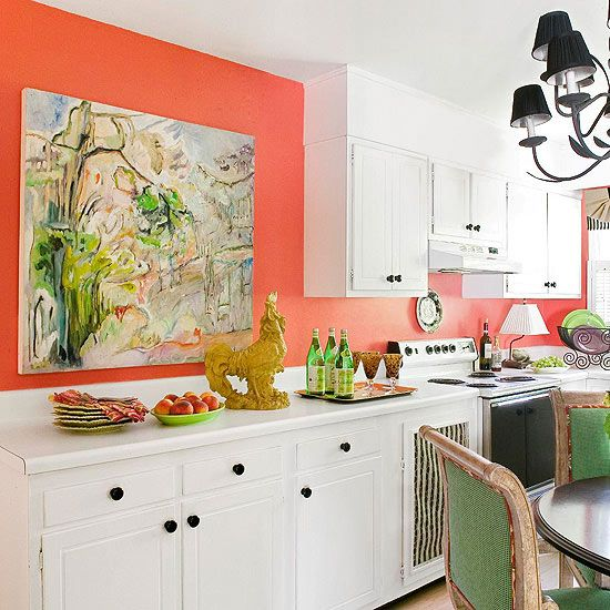 Stick to the Walls:If you want to experiment with an unusual color in your kitchen, limit yourself to surfaces that can be altered easily so you can make changes later. A bold wash of coral covers the wall and backsplash in this beach kitchen. A large piece of artwork brings in greens, which repeat in dishware and chair upholstery, creating a fresh and lively color scheme.