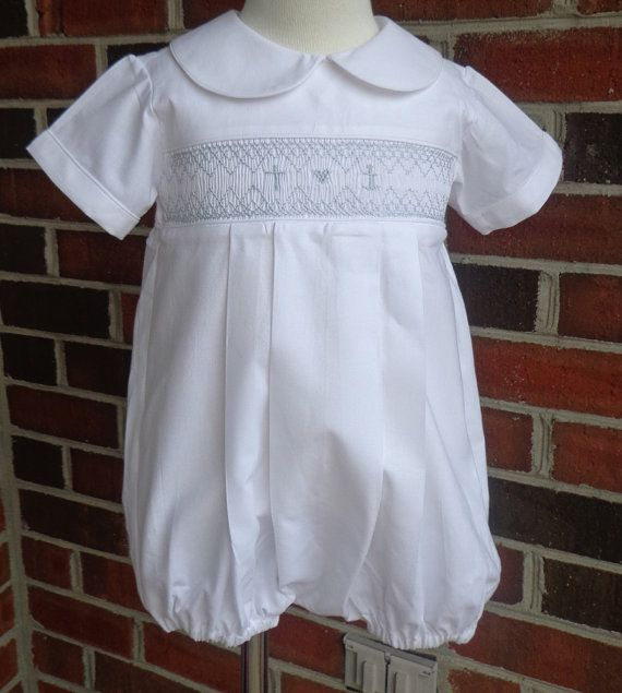 This hand smocked baby baptism outfit is made from 100% cotton. It is a bubble suit style. It can be made in sizes 3 months to 24 months. The smocking design is of a cross, an anchor and a heart, which represents faith , hope and love. If you prefer, I can do your babys initials along with a cross or your babys initials alone. I have two color choices pictured, white on white and blue smocking on white. This outfit can be made with or without a collar.The outfit buttons in the back and it…