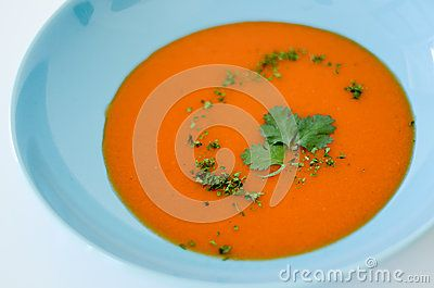 Food, tomato or gaspacho, on blue plate over white background